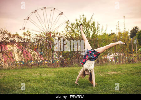 Young woman cartwheeling at Westford apple blossom carnival, Massachusetts USA - Stock Photo