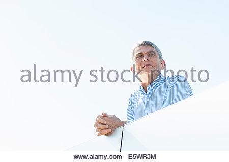 Senior adult businessman leaning on balcony - Stock Photo