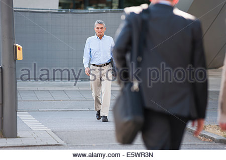 Senior adult businessman walking down street - Stock Photo