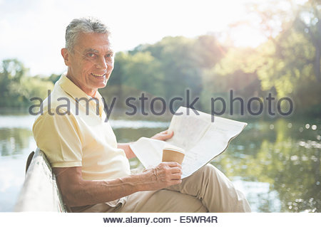 Senior adult man sitting by lake, holding coffee and newspaper - Stock Photo