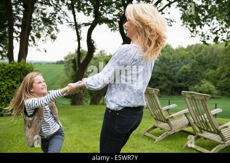 Mother and daughter holding hands - Stock Photo