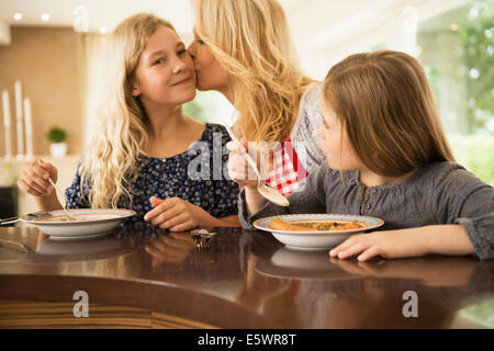 Mother kissing daughter on cheek - Stock Photo