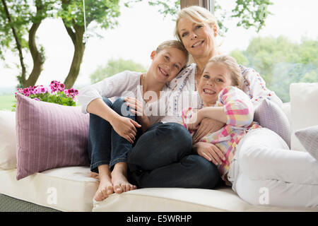 Mother and daughters sitting on sofa - Stock Photo