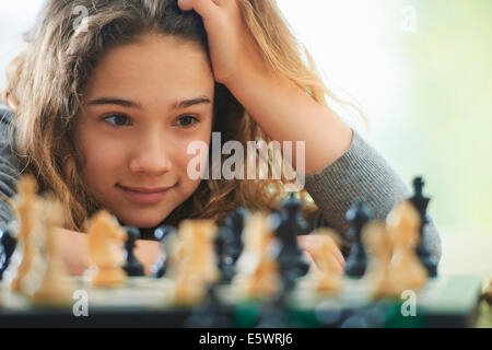 Portrait of young girl playing chess - Stock Photo