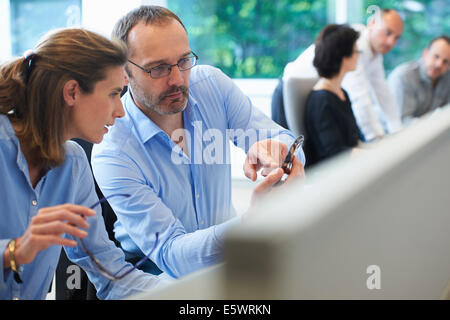Colleagues looking at mobile phone - Stock Photo