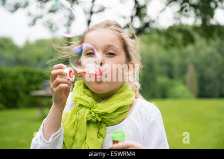 Girl blowing bubbles - Stock Photo