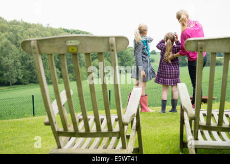 Mother and daughters using binoculars, chairs in foreground - Stock Photo