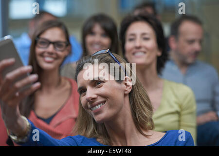 Group of people taking self portrait photograph - Stock Photo