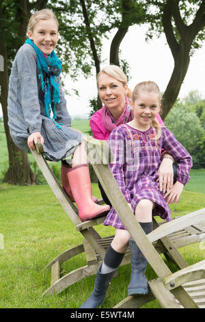 Mother and daughters sitting on wooden chair, portrait - Stock Photo