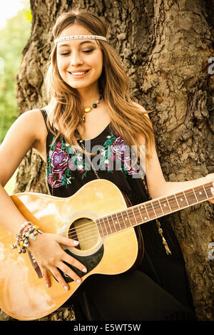 Young hippy woman playing guitar - Stock Photo