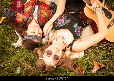 Hippy girls lying in field with guitar - Stock Photo