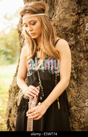 Hippy woman with guitar looking sad standing by tree - Stock Photo
