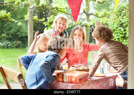 Family singing and cheering at birthday party - Stock Photo