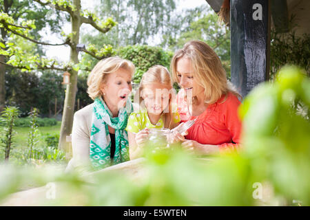 Girl opening jar of coins with family - Stock Photo
