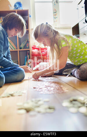 Brother and sister counting coins from savings jar - Stock Photo