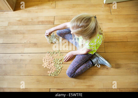 Girl counting coins from savings jar - Stock Photo