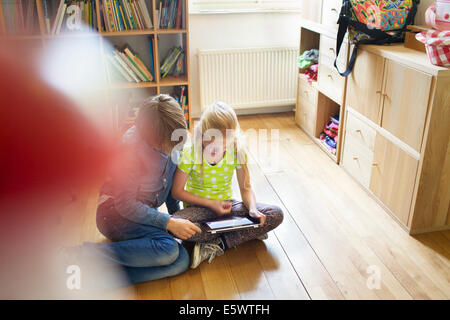 Brother and sister sharing and using digital tablet - Stock Photo