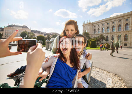 Young adult woman taking picture of friends - Stock Photo