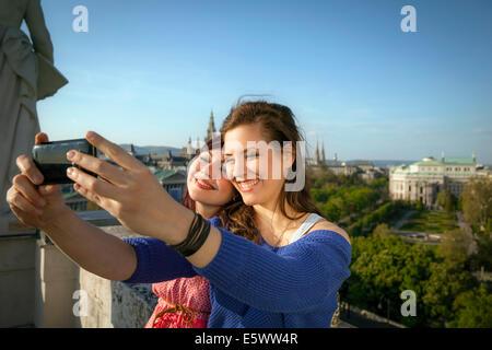 Two young women taking self portrait, Vienna, Austria - Stock Photo
