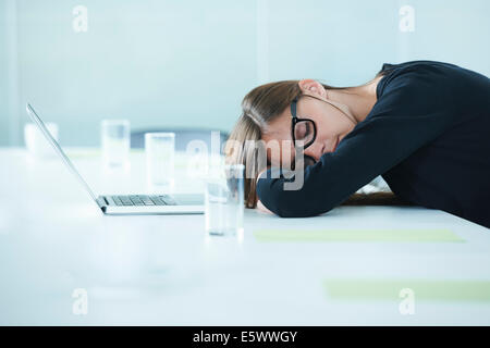Female office worker asleep at conference table - Stock Photo