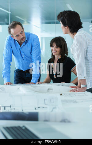Architect showing client blueprints on boardroom table - Stock Photo