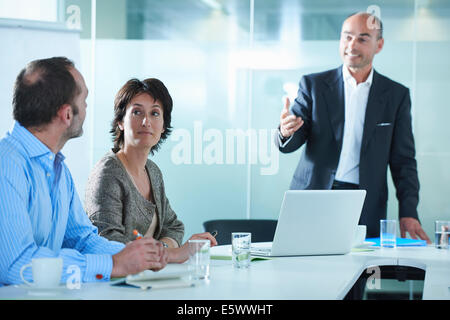 Businessmen and women arguing across boardroom table - Stock Photo