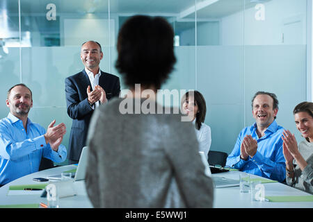 Businessmen and women applauding around boardroom table - Stock Photo