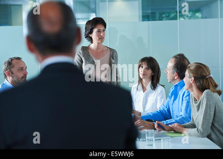 Businessmen and women arguing around boardroom table - Stock Photo