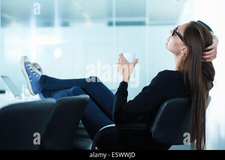 Female office worker leaning back with feet up on conference table - Stock Photo