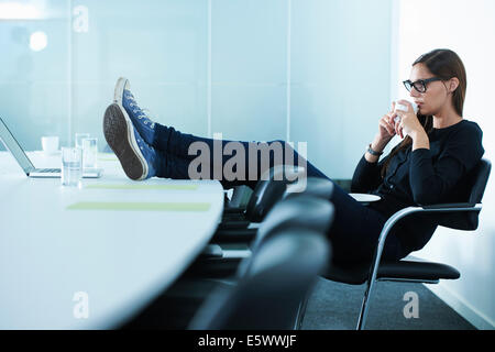 Female office worker drinking coffee with feet up on conference table - Stock Photo