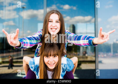 Two young women piggybacking making I love you hand gesture - Stock Photo