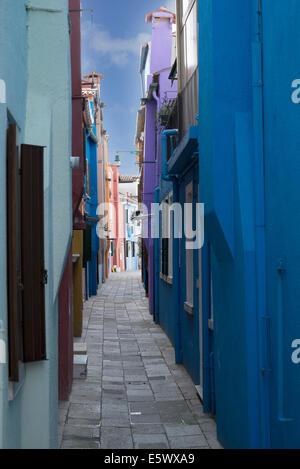 Multi colored houses in narrow alley, Burano, Venice, Veneto, Italy - Stock Photo