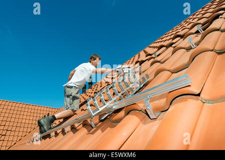 Worker installing framework for solar roof panels on new home, Netherlands - Stock Photo