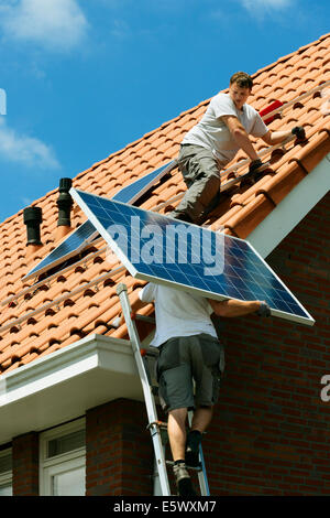 Workers carrying and installing solar panels on roof of new home, Netherlands - Stock Photo