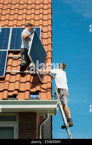 Workers installing solar panels on roof of new home, Netherlands - Stock Photo