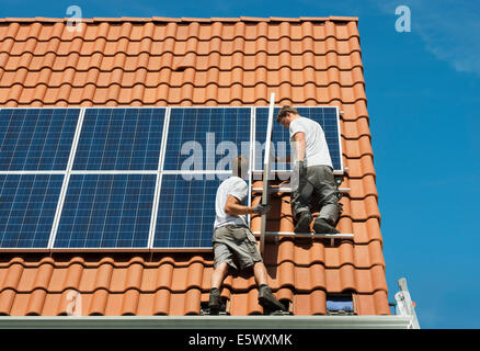 Workers installing solar panels on roof framework of new home, Netherlands - Stock Photo