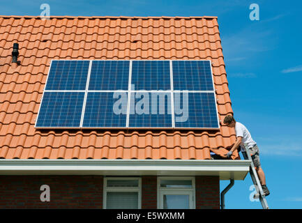 Worker checking installation of solar panels on roof of new home, Netherlands - Stock Photo