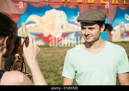 Young couple photographing on SLR camera at funfair - Stock Photo