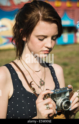 Young woman photographing on SLR camera at funfair - Stock Photo