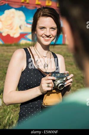 Young couple taking photographs on SLR camera at funfair - Stock Photo
