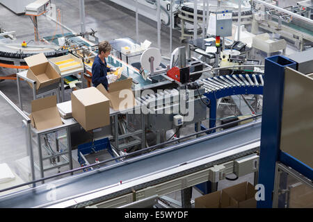 Mature woman working in paper packaging factory - Stock Photo
