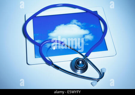 Acoustic stethoscope and digital tablet displaying a cloud - Stock Photo