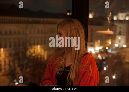 Young woman enjoying view from hotel room, Vienna, Austria - Stock Photo