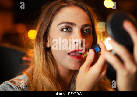 Beautiful young woman applying lipstick in city taxi at night - Stock Photo