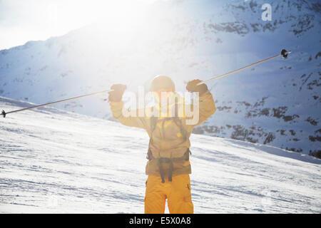 Mid adult male skier holding up ski poles in celebration, Austria - Stock Photo