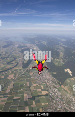Female skydiver free falling upside down over Grenchen, Berne, Switzerland - Stock Photo