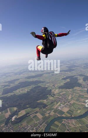 Female skydiver free falling over Grenchen, Berne, Switzerland - Stock Photo