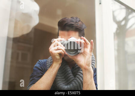 Portrait of young man photographing with SLR camera - Stock Photo
