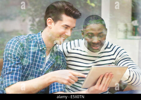 Two young male friends looking at digital tablet behind window - Stock Photo