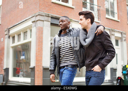 Two young men strolling down the street with arms around each other - Stock Photo